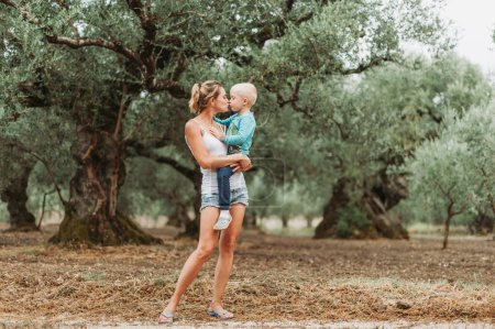 Photo for The boy in the arms of his mother in an olive grove. - Royalty Free Image