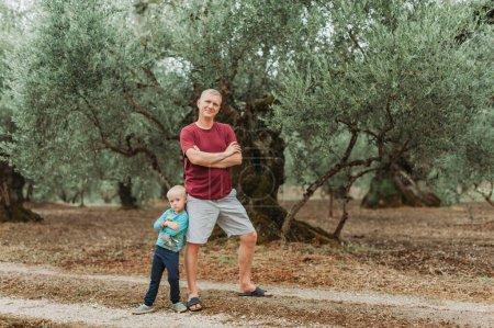 Photo pour Le garçon avec son père debout dans une oliveraie, Grèce. - image libre de droit
