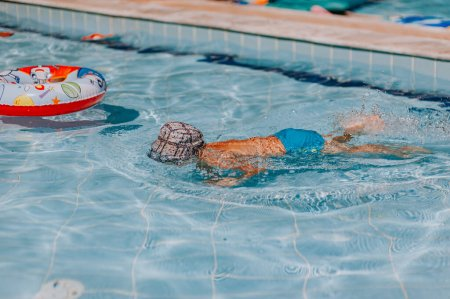 Photo for Happy young boy swim and dive underwater, kid breast stroke with fun in pool. Active healthy lifestyle, water sport activity and lessons with parents on summer family vacation with child. - Royalty Free Image