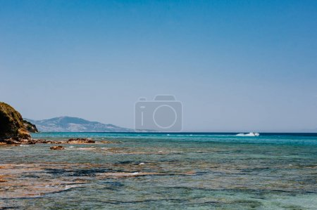 Photo for Peaceful beach with golden island and sand at sunset, sea with calm water, Greece - Royalty Free Image