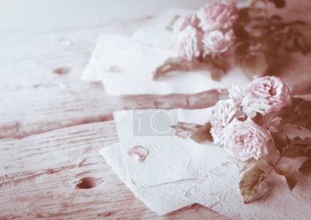 Photo pour Roses roses sur fond de table en bois avec verres rétro et papier blanc fait à la main comme espace de copie, thème floral romantique - image libre de droit