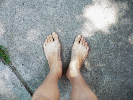 two barefoot legs on concrete floor