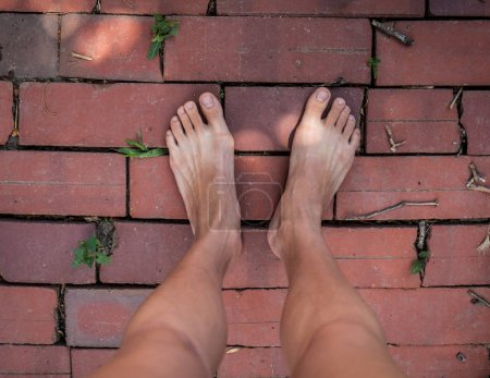two barefoot legs on red brick floor, outdoor background