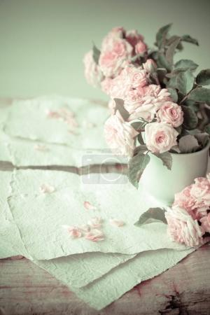 Pink roses with white hand made paper on wooden table background