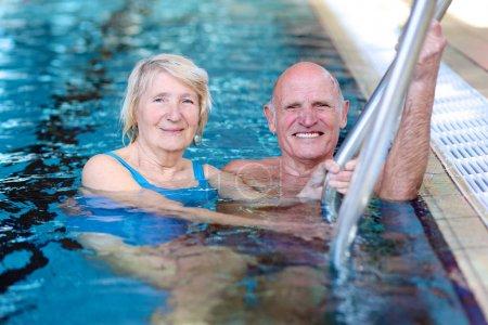 Photo pour Heureux couple senior active saine s'amuser ensemble dans la piscine - image libre de droit