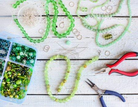Photo pour Table de travail avec perles et instruments pour la fabrication de bijoux - image libre de droit