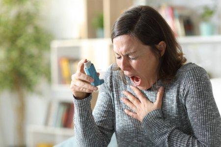 Mujer adulta asmática sufre ataque de asma sosteniendo inhalador sentado en el sofá en casa