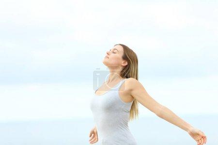 Mujer respirando aire fresco extendiendo los brazos de pie en la playa