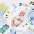 Baby on white background with clothing, toiletries...