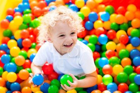 Foto de Niño riendo felices divirtiéndose en el hoyo de la bola en la fiesta de cumpleaños en Parque de atracciones de niños y centro de interior del juego. Niño jugando con las bolas de colores en parque infantil piscina de bolas. Juguetes de actividad para el niño pequeño. - Imagen libre de derechos