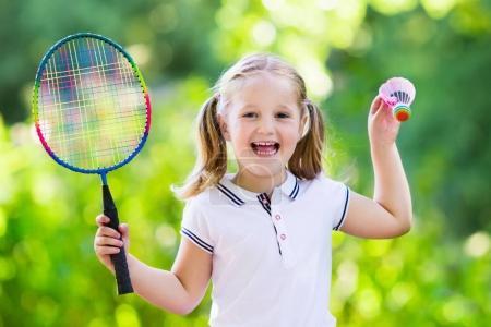 Photo pour Active fille préscolaire jouant au badminton en plein air cour en été. Les enfants jouent au tennis. Sports scolaires pour enfants. Sport de raquette et de navette pour enfant athlète. Enfant avec raquette et navette . - image libre de droit