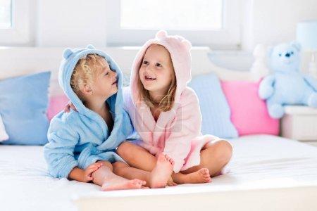 Photo pour Joyeux rire enfants, garçon et fille en peignoir doux après le bain jouer sur lit blanc avec des oreillers bleus et roses dans la chambre ensoleillée. Enfant en serviette propre et sèche. Lavage, hygiène infantile, santé et soins de la peau . - image libre de droit