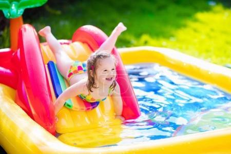 Foto de Niños jugando en la piscina inflable del bebé. Los niños nadan y splash en centro de juegos de jardín colorido. Niña feliz jugando con juguetes de agua en un día caluroso de verano. Familia que se divierten al aire libre en el patio trasero. - Imagen libre de derechos
