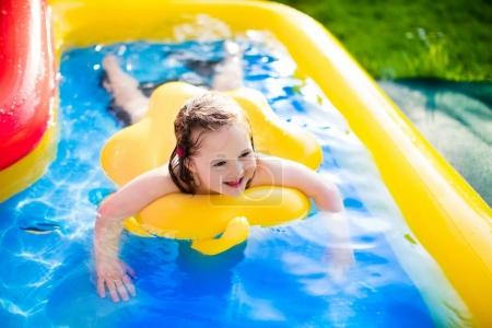 Little girl playing in inflatable garden swimming pool