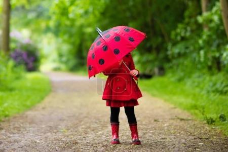 Photo pour Petite fille jouant dans un parc d'été pluvieux. Enfant avec parapluie coccinelle rouge, manteau imperméable et bottes sautant dans la flaque et la boue sous la pluie. Enfant marchant dans la douche d'automne. Amusement en plein air par tous les temps . - image libre de droit