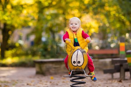 Photo for Kids on playground Children play in autumn park. Child on slide and swing on sunny fall day. Preschool or kindergarten yard. Daycare for young kid. Baby on play ground. Outdoor fun in autumn. - Royalty Free Image