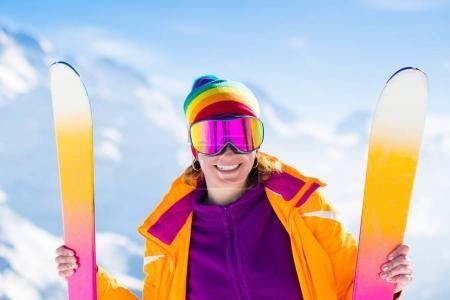 Photo pour Jeune femme active skiant en montagne. Enfant skieuse avec casque de sécurité, lunettes et bâtons profitant d'une journée d'hiver ensoleillée dans les Alpes suisses. Course de ski pour adultes. Sports d'hiver et de neige en station alpine . - image libre de droit