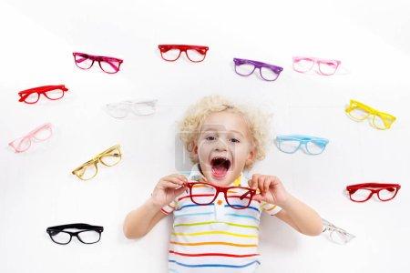 Photo pour Test visuel enfant à œil. Petit enfant qui choisit des lunettes dans un magasin d'opticiens. Mesure de la vue pour les écoliers. Vêtements oculaires pour enfants. Médecin qui vérifie les yeux. Bébé avec lunettes vue de dessus . - image libre de droit