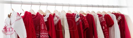 Photo for Clothes rack with red Christmas knit wear. Wardrobe with knitted winter jumper and dress. Xmas clothing collection. Christmas gifts shopping. Winter sale for children wear. Kids clothing shop - Royalty Free Image
