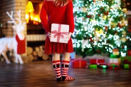 Child at Christmas tree. Kid at fireplace on Xmas