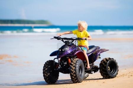 Photo pour Petit garçon CIRC. motos quad sur la plage tropicale. Mignon enfant bouclé blond sur quadricycle. Trajet en véhicule tout-terrain. Sports mécaniques de croix sur la dune de sable de l'océan. Activité de vacances d'été enfants. Hors course sur route. - image libre de droit