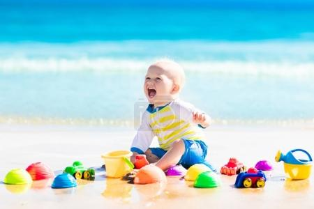 Baby playing on tropical beach digging in sand