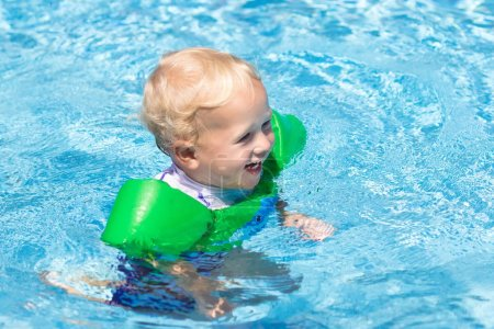 Baby with inflatable armbands in swimming pool.