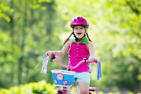 Photo pour Enfant à vélo. Enfant à vélo dans un parc ensoleillé. Petite fille appréciant la balade à vélo sur son chemin vers l'école par une chaude journée d'été. Les enfants d'âge préscolaire apprennent à s'équilibrer à vélo dans un casque sûr. Sport pour enfants . - image libre de droit
