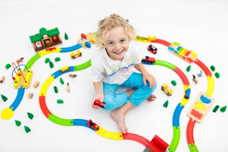 Photo for Kids play with toy train railway. Child playing with colorful rainbow wooden trains. Toys for little boy. Preschooler building rail road at home or daycare, preschool. Kindergarten educational games. - Royalty Free Image
