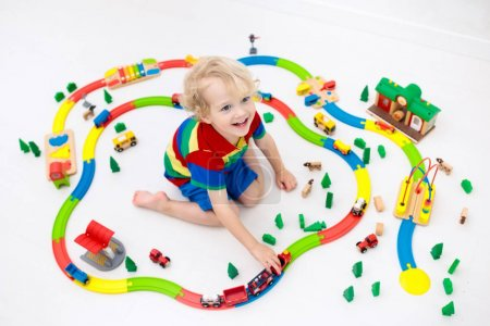 Kids play with toy train railway. Child playing with colorful rainbow wooden trains. Toys for little boy. Preschooler building rail road at home or daycare, preschool. Kindergarten educational games.