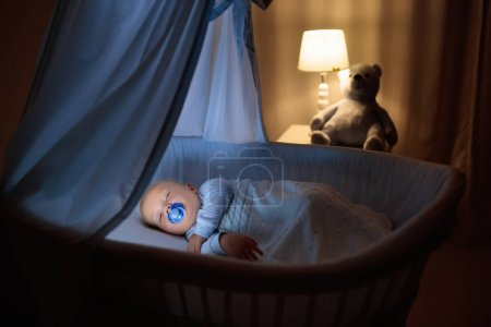 Adorable baby with pacifier sleeping in blue bassinet with canopy at night. Little boy in pajamas taking a nap in dark room with crib, lamp and toy bear. Bed time for kids. Bedroom and nursery interior.