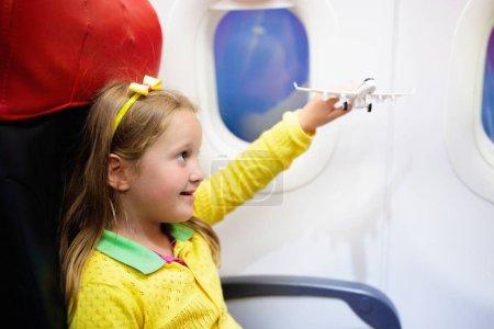 Photo pour Enfant dans l'avion. Enfant dans un avion assis dans un siège de fenêtre. Animations de vol pour enfants. Voyager avec de jeunes enfants. Les enfants volent et voyagent. Vacances d'été en famille. Petite fille avec jouet en avion - image libre de droit