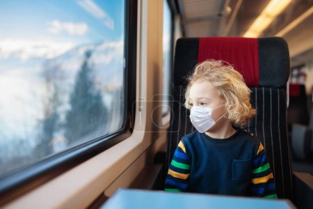 Photo for Child in train in face mask. Virus outbreak. Coronavirus and flu pandemic. Safe travel with young child and baby. Little boy sitting in passenger car of railroad wagon wearing surgical mask. - Royalty Free Image