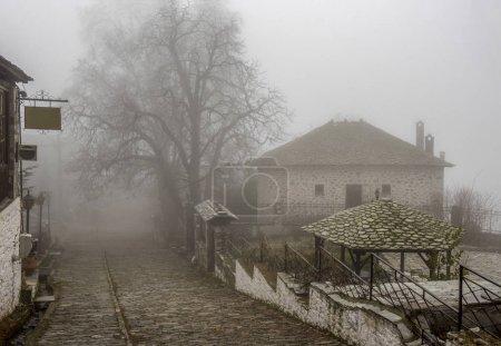Fog and traditional stone houses in Vizitsa village on mountain Pelion. Greece.