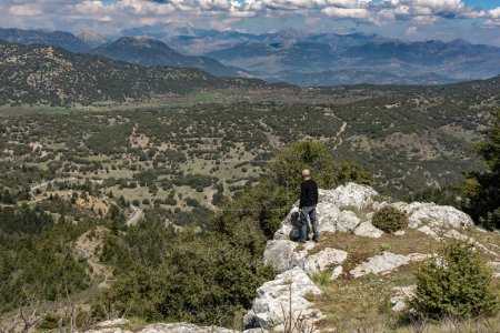 Man standing on rocks and enjoy the breathless view on Mainal mountain , Greece.
