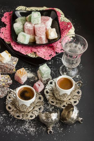Photo for Close-up shot of delicious Turkish delight or lokum and turkish coffee on black surface - Royalty Free Image