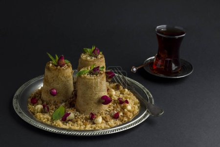 Photo pour Gros plan d'une délicieuse baklava turque aux boutons de roses et de noix avec une tasse de thé sur table blanche - image libre de droit