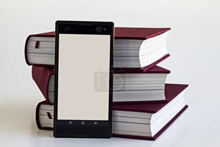 Photo for Close-up shot of stack of books and smartphone on white tabletop - Royalty Free Image