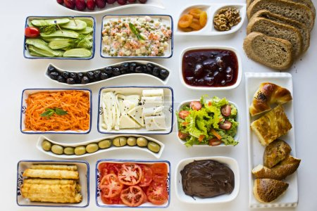 Photo for Close-up shot of various delicious food in various plates on white iftar table - Royalty Free Image