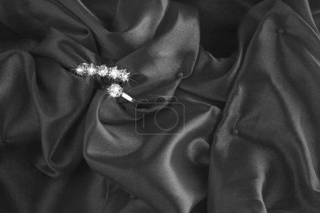 Five stone diamond ring on red satin fabric.Top vi...