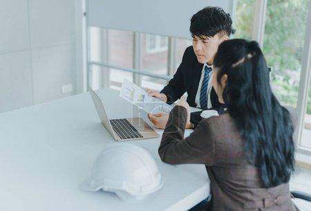 Photo pour Des collègues asiatiques, hommes et femmes, discutent de travail avec du papier quadrillé et un carnet. - image libre de droit