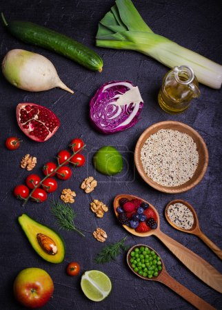 Selection of healthy food. Food background: quinoa, pomegranate, lime, green peas, berries, avocado, nuts and olive oil. Slate banner background. overhead, vertical