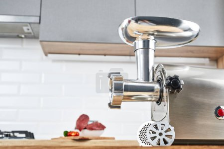 Meat grinder with fresh meat on a wooden table in modern kitchen interior