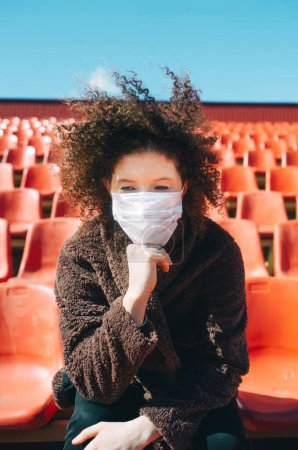 Photo for Curly girl in a medical mask in city stadium thinking about how to stop the coronavirus epidemic and what to do. Thinks about the dangers of this. COVID-19 - Royalty Free Image