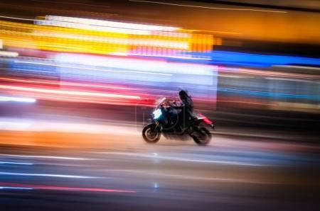 Black motorcycle running fast through the nightlit streets of a large metropolitan city