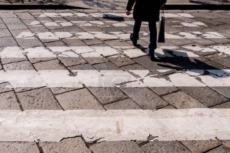 man crossing city street at crossroad choice sign.