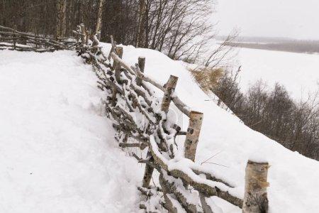 clôture en bois d'osier sur la rive escarpée d'une rivière gelée .