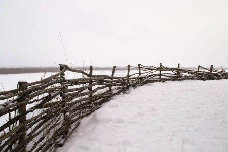 clôture en bois d'osier sur la rive escarpée d'une rivière gelée. Hiver Arkhangelsk région