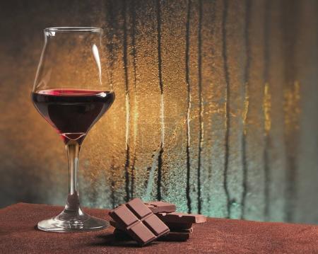 Red wine glass with chocolate and rainy windowpane