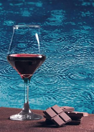 Red wine glass with chocolate and blue rain circles